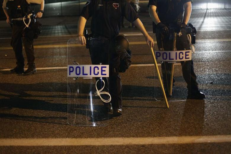 Police officers in riot gear stand in position as demonstrators protest the shooting death of Michael Brown, in Ferguson, Missouri August 19, 2014. REUTERS/Joshua Lott