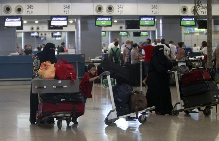 Passengers handle their luggage at a check-in counter in Cairo Airport, in ile photo.REUTERS/Mohamed Abd El Ghany