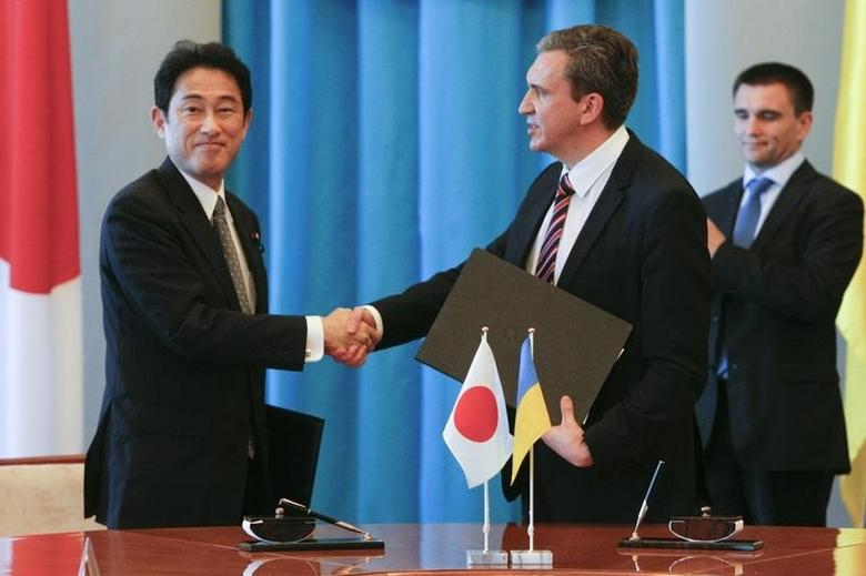 Minister of Economic Development and Trade of Ukraine Pavlo Sheremeta (C) shakes hands with Japan's Foreign Minister Fumio Kishida during a meeting in Kiev July 17, 2014. REUTERS/Valentyn Ogirenko