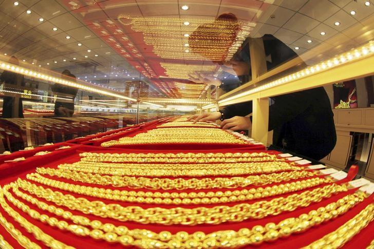 A sales assistant arranges gold necklaces at a store in Lianyungang, Jiangsu province, January 23, 2014. REUTERS/China Daily