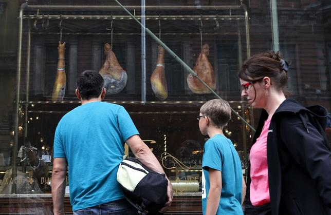 People pass by a shop window displaying Spanish ham for sale at a grocery store in St. Petersburg August 13, 2014. REUTERS/Alexander Demianchuk