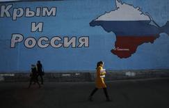 Люди проходят мимо нарисованной на стене карты Крыма в Москве 25 марта 2014 года. Союз европейских футбольных ассоциаций отказался признавать матчи команд Крыма, присоединенного Россией, в соревнованиях под эгидой Российского футбольного союза, говорится в сообщении на сайте УЕФА. REUTERS/Artur Bainozarov