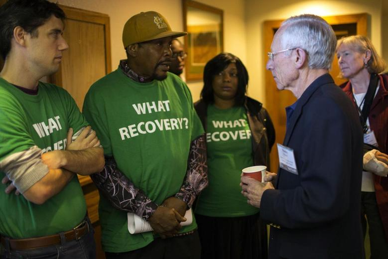 Stanley Fischer (2nd R), vice chairman of the Federal Reserve System, speaks with demonstrator Reginald Rounds from Ferguson, Missouri at the Jackson Hole Economic Policy Symposium in Jackson Hole, Wyoming August 22, 2014. REUTERS/David Stubbs