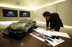 Infiniti chief designer Alfonso Albaisa draws a sketch of a car next to a quarter sized model of the Infiniti Emerg E car during an interview with Reuters at Nissan Technical Center in Atsugi, south of Tokyo May 20, 2014. REUTERS/Yuya Shino/Files