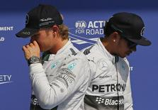 Mercedes Formula One driver Nico Rosberg (L) of Germany and team mate Lewis Hamilton of Britain walk next to each other after the qualifying session at the Belgian F1 Grand Prix in Spa-Francorchamps August 23, 2014.   REUTERS/Yves Herman