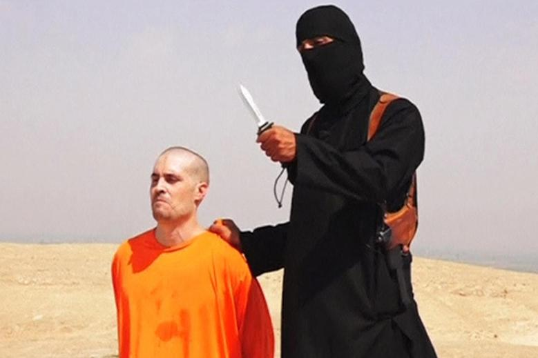 A masked Islamic State militant holding a knife speaks next to man purported to be U.S. journalist James Foley at an unknown location in this still file image from an undated video posted on a social media website.  REUTERS/Social Media Website via REUTERS TV/Files