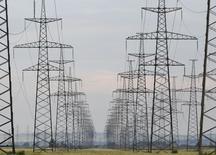 Высоковольтные линии электропередачи у Саяно-Шушенской ГЭС в Хакасии 28 июля 2014 года. Российский энергохолдинг ИнтерРАО заработал прибыль в январе-июне 2014 года против убытка в прошлом году, связанного с обесценением, и начал поиск средств для исполнения требований по опциону с ВЭБом на $1 миллиард. REUTERS/Ilya Naymushin