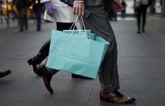Человек с пакетом Tiffany & Co. в Нью-Йорке 4 апреля 2013 года. Ювелир Tiffany & Co вновь повысил годовой прогноз после публикации оказавшегося лучше прогнозов квартального отчета, на котором положительно отразились сильные продажи в Южной, Центральной и Северной Америке, а также странах Азиатско-Тихоокеанского региона. REUTERS/Mike Segar