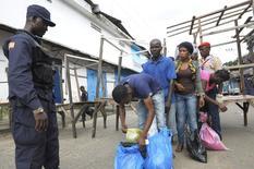 Fuerzas de seguridad realizan un control en un área de cuarentena de ébola en Monrovia, ago 23 2014. El brote del ébola está causando un enorme daño a las economías de África Occidental, drenando sus recursos presupuestarios y recortando su crecimiento en un 4 por ciento a medida que los empresarios extranjeros se van y son cancelados proyectos, dijo el presidente del Banco Africano de Desarrollo (BAfD). REUTERS/2Tango