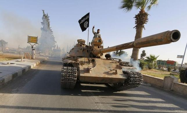Militant Islamist fighters on a tank take part in a military parade along the streets of northern Raqqa province June 30, 2014. REUTERS/Stringer
