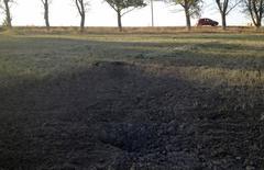 Воронка от снаряда под Новоазовском 24 августа 2014 года. В понедельник жительница города Новоазовска в юго-восточной части Украины сказала, что видела подходящую к городу колонну бронетехники, которая открыла огонь. REUTERS/Maria Tsvetkova