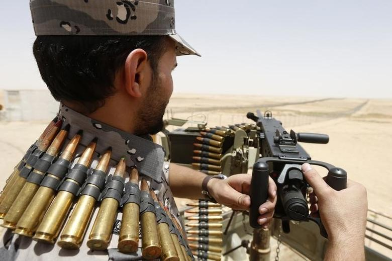 A member of the Saudi border guards force man a machine gun mounted on a military truck positioned on Saudi Arabia's northern borderline with Iraq July 14, 2014.  REUTERS/Faisal Al Nasser