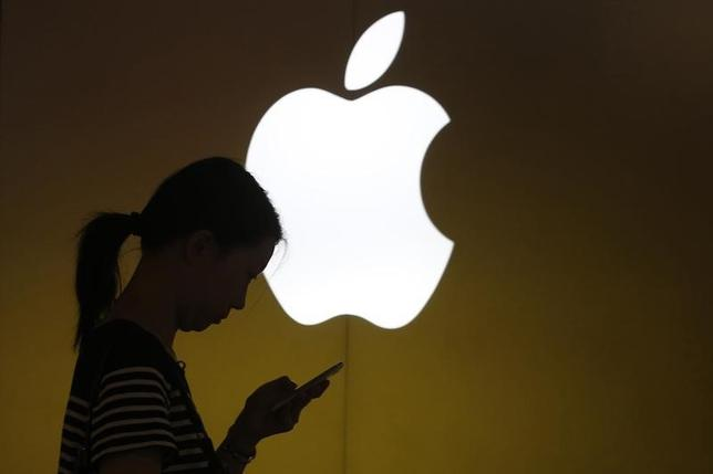 A woman looks at the screen of her mobile phone in front of an Apple logo outside its store in downtown Shanghai September 10, 2013.   REUTERS/Aly Song