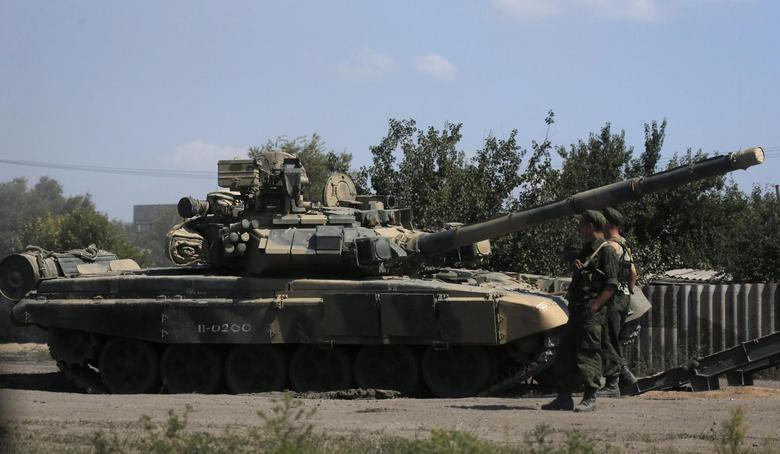 Russian soldiers are pictured next to a tank in Kamensk-Shakhtinsky, Rostov region, near the border with Ukraine, August 23, 2014.  REUTERS/Alexander Demianchuk