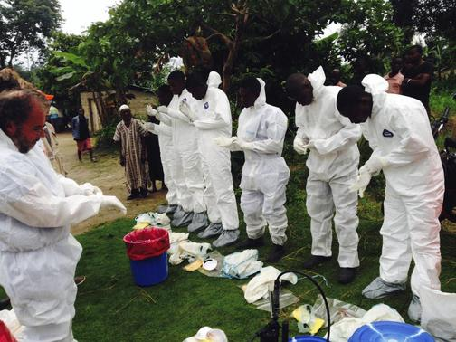 Volunteers prepare to remove the bodies of people who were suspected of contracting Ebola and died in the community in the village of Pendebu, north of Kenema July 18, 2014.  REUTERS/WHO/Tarik Jasarevic