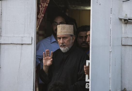 Tahir ul-Qadri, Sufi cleric and leader of political party Pakistan Awami Tehreek (PAT),waves to supporters as he walks out his container to address supporters in front of the Parliament house building during the Revolution March in Islamabad August 28, 2014. REUTERS-Faisal Mahmood