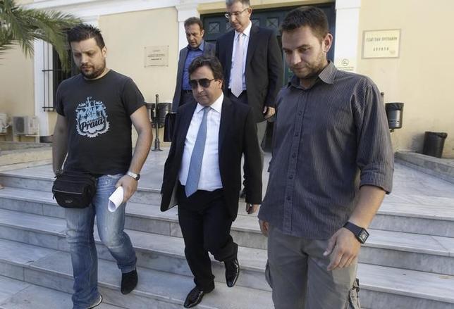 Greek shipowner Victor Restis (C) leaves a court in Athens July 23, 2013. REUTERS/John Kolesidis