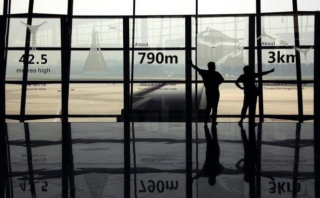 Two people watch planes land as they stand in the terminal three building of the Beijing Capital International Airport July 11, 2011. REUTERS/David Gray