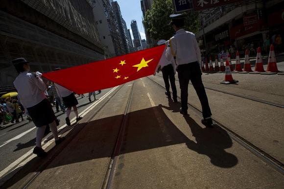 Youth uniformed group members carry a Chinese national flag during a march in the streets to demonstrate against a pro-democracy Occupy Central campaign in Hong Kong August 17, 2014. REUTERS/Tyrone Siu