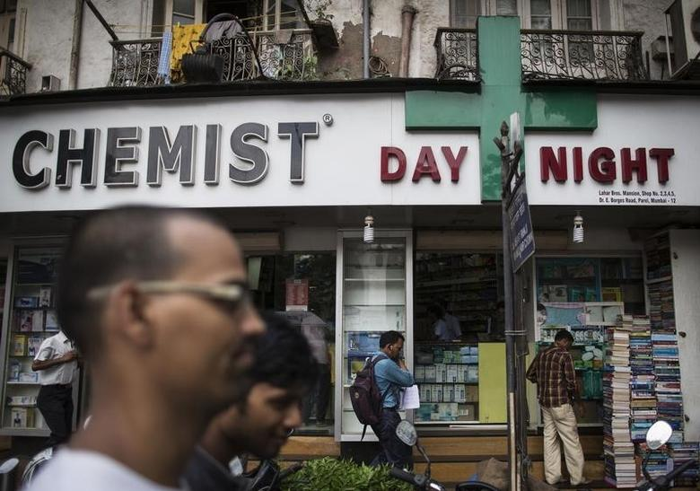 People walk past a chemist shop at a market in Mumbai June 24, 2014.  REUTERS/Danish Siddiqui