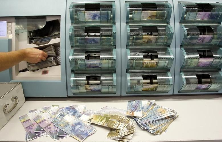 A bank clerk places Swiss franc banknotes of several values to be sorted in a money counter in a bank in Zurich August 16, 2011. REUTERS/Arnd Wiegmann