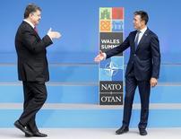 El secretario general de la OTAN, Anders Fogh Rasmussen, saluda al presidente de Ucrania, Petro Poroshenko, al inicio de la cumbre de la Alianza Militar de Occidente, cerca de Newport. 4 septiembre, 2014. El secretario general de la OTAN, Anders Fogh Rasmussen, dijo el jueves que Rusia está atacando a Ucrania, elevando el tono de la retórica occidental contra Moscú al inicio de una cumbre de la alianza liderada por Estados Unidos. REUTERS/Andrew Winning