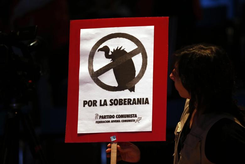 A woman looks at a sign with a drawing of a vulture that reads ''For sovereignty'' during a rally against the payment to what the government calls ''vulture'' creditors in Buenos Aires, August 12, 2014.   REUTERS/Marcos Brindicci