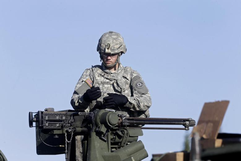 A U.S. second cavalry regiment soldier inspects a weapon on an armoured personal carrier during the ''Steadfast Javelin II'' military exercise in the Lielvarde air base, September 6, 2014. REUTERS/Ints Kalnins