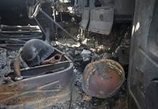 Военные каски в кабине сгоревшего грузовика под Мариуполем 7 сентября 2014 года. Число людей, погибших в результате украинского конфликта, превысило 3.000, если включить жертв падения малайзийского боинга, сообщил в понедельник представитель ООН. REUTERS/Vasily Fedosenko