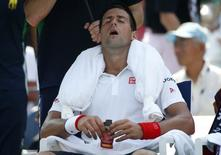 Novak Djokovic of Serbia cools off with an ice towel during a break in play against Kei Nishikori of Japan in their semi-final match at the 2014 U.S. Open tennis tournament in New York, September 6, 2014.         REUTERS/Mike Segar