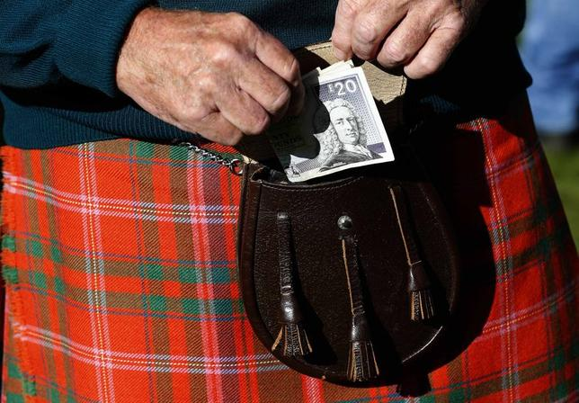 A man puts money in his sporran at the Birnam Highland Games in Scotland, August 30, 2014. REUTERS/Russell Cheyne