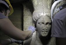 Archaeologists work on a sculpted female figure, known as Caryatid, inside a site of an archaeological excavation at the town of Amphipolis, in northern Greece, in this handout photo taken September 6, 2014, and distributed by Greece's Culture ministry. REUTERS/Hellenic Culture Ministry/Handoutb via Reuters