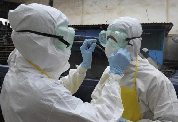 Os profissionais de saúde vestindo roupas de proteção preparar-se antes de realizar um cadáver abandonado apresentando sintomas do Ebola no mercado Duwala em Monrovia 17 de agosto de 2014 REUTERS / 2Tango