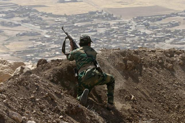 A Kurdish Peshmerga fighter moves into position while firing into Baretle village (background), which is controlled by the Islamic State, in Khazir, on the edge of Mosul September 8, 2014. REUTERS/Ahmed Jadallah
