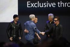 Apple CEO Tim Cook speaks with U2 during an Apple event announcing the iPhone 6 and the Apple Watch at the Flint Center in Cupertino, California, September 9, 2014. REUTERS/Stephen Lam