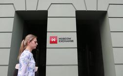 Женщина проходит мимо здания Московской биржи 1 августа 2014 года. Российские фондовые индексы в четверг продолжают осваивать сложившиеся уровни на фоне сохраняющейся неопределенности относительно западных санкций и перед экспирацией срочных контрактов в понедельник. REUTERS/Maxim Shemetov