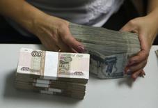Сотрудник банка пересчитывает рублевые купюры в Москве 2 сентября 2014 года. Рубль обновил исторический минимум после известий о новых санкциях против России, которые европейские лидеры договорились применить до конца недели. REUTERS/Maxim Zmeyev