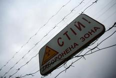 Предупреждающий знак у Чернобыльской АЭС 28 мая 2006 года. Атомная монополия Украины Энергоатом, которая пытается снизить зависимость от российского Росатома из-за конфликта между странами, планирует с 2015 года загрузить один из ядерных блоков топливом американского производства, а также ищет новых инвесторов для строительства двух новых энергоблоков, сообщил Энергоатом Рейтер. REUTERS/Damir Sagolj