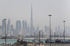The skyline is seen with the Burj Khalifa as ships dock at Port Rashid, in Dubai May 26, 2013. REUTERS/Ahmed Jadallah