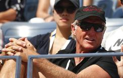 Golfer Greg Norman of Australia watches the fourth round match between Grigor Dimitrov of Bulgaria and Gael Monfils of France at the 2014 U.S. Open tennis tournament in New York, September 2, 2014. REUTERS/Adam Hunger