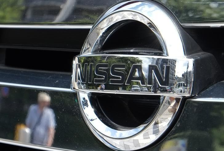 A pedestrian and cars are reflected in a Nissan Motor logo at the company's dealership in Tokyo July 28, 2014. REUTERS/Toru Hanai