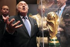 FIFA President Sepp Blatter gestures next to the World Cup trophy after a media conference in Sao Paulo June 5, 2014.   REUTERS/Paulo Whitaker