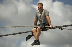 High wire walker Nik Wallenda talks with spectators as he balances on a 1,200 foot-long (366 meter) cable during a practice session in Sarasota, Florida, June 14, 2013.    REUTERS/Steve Nesius
