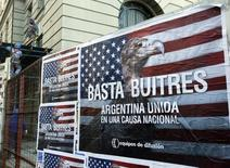 "Construction workers work near posters that read ""Enough vultures, Argentina united for a national cause"" in Buenos Aires June 18, 2014. REUTERS/Enrique Marcarian"