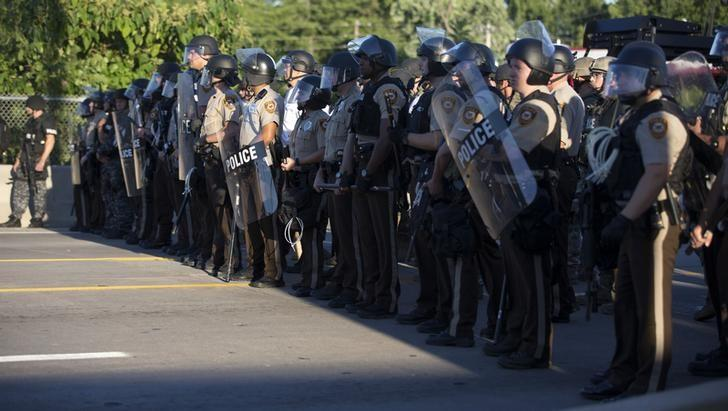 Police officers keep watch while demonstrators (not pictured) protest the death of black teenager Michael Brown in Ferguson, Missouri August 12, 2014. REUTERS/Mario Anzuoni