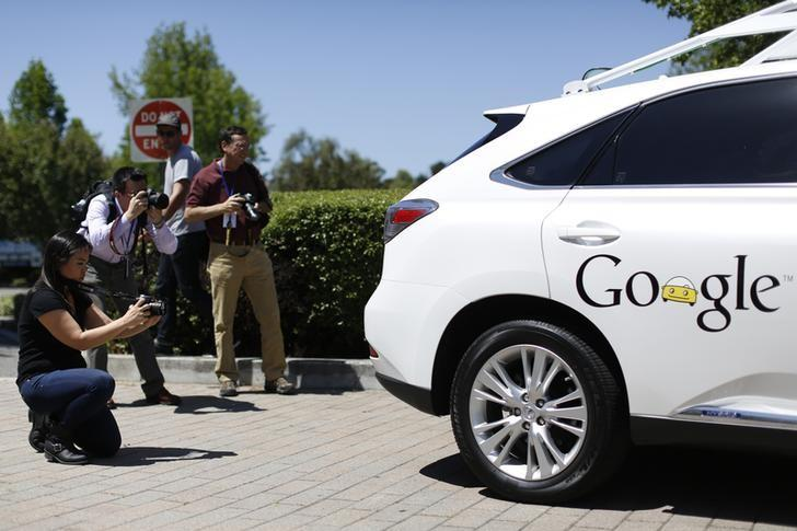 Members of the media take photos of a Google self-driving vehicle at the Computer History Museum after a presentation in Mountain View, California May 13, 2014. REUTERS/Stephen Lam