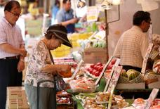 A woman rummages through her purse in front of a vegetable store at a shopping district in Tokyo July 29, 2014.  REUTERS/Yuya Shino