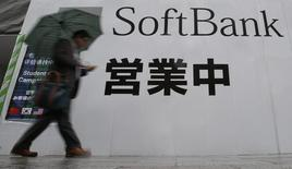 A man holding an umbrella walks past the logo of Softbank Corp at its branch in Tokyo April 22, 2014. REUTERS/Yuya Shino/Files