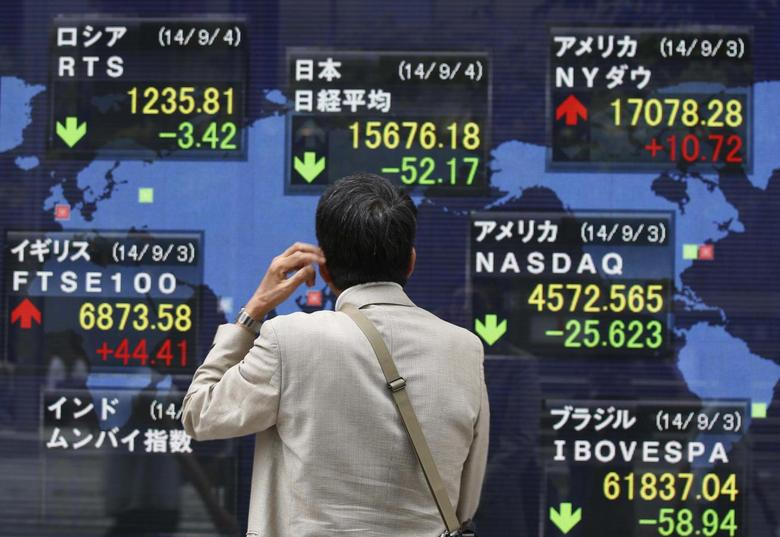 A man looks at an electronic board displaying Japan's Nikkei average (top C) and the stock price indexes of various countries outside a brokerage in Tokyo September 4, 2014.  REUTERS/Issei Kato