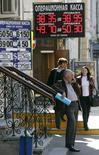 Вывески пунктов обмена валюты в Москве 16 сентября 2014 года. Рубль торгуется с минимальными изменениями утром вторника; сессия началась укреплением на фоне позитивных тенденций после данных о росте китайской промышленности и в ожидании уплаты НДПИ, однако спрос на валюту для погашения внешних займов в условиях затрудненного доступа к западным ресурсам ограничивает позитивные тенденции. REUTERS/Sergei Karpukhin